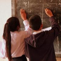 Mädchen und Junge rechnen an der Schultafel